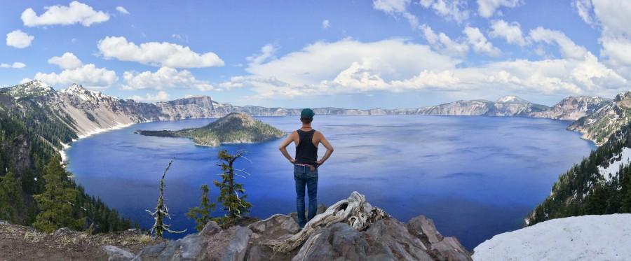 Ich stehe auf einem Vorsprung und blicke auf den dunkelblauen Crater Lake herunter.